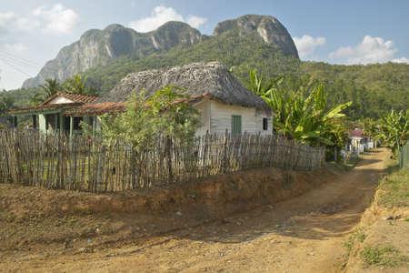 Pequeñas casas en frente de las montañas de piedra caliza en el Valle de Viales, en el centro de Cuba Foto de archivo