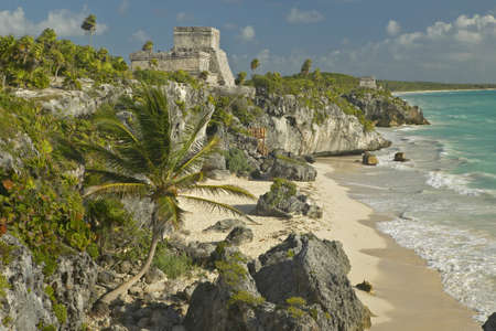 Mayan ruins of Ruinas de Tulum (Tulum Ruins) in Quintana Roo, Mexico. El Castillo is pictured in Mayan ruin in the Yucatan Peninsula, Mexico at sunset, with beach and Caribbean Sea to right
