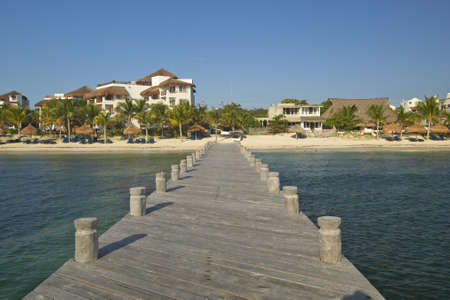 morelos: Dock in water looks back at Puerto Morelos, Mexico, South of Cancun in the Yucatan Peninsula, Mexico