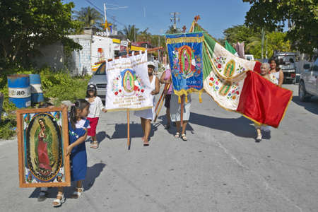 Older women and children marching through streets of Puerto Morelos carrying Mexican flag and Virgen de Guadalupe, Yucatan Peninsula, Mexico