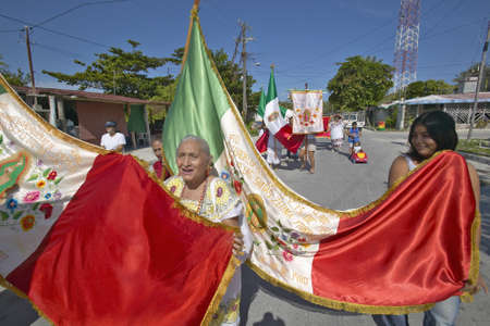 morelos: Older women and children marching through streets of Puerto Morelos carrying Mexican flag and Catholic statues, Yucatan Peninsula, Mexico, south of Cancun