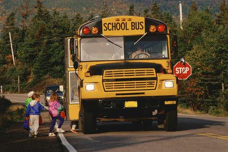 motorbus: Children boarding a yellow school bus, New England