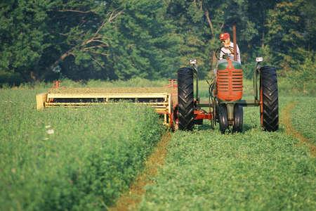 Farmer on a tractor harvesting a field Sajtókép
