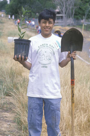 A teenage boy holding a plant and a shovel during Earth Day participation Stock Photo - 20711692