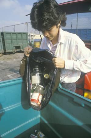 poubelle bleue: Un gar�on de vider les mati�res recyclables dans un bac bleu dans un centre de recyclage