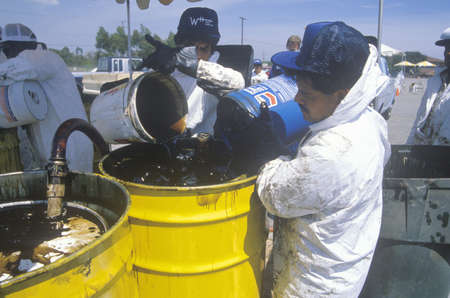 Workers handling toxic household wastes at waste cleanup site on Earth Day at the Unocal plant in Wilmington, Los Angeles, CA