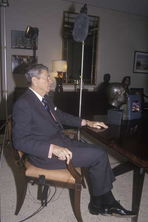 ronald reagan: President Ronald Reagan seated and preparing for an interview