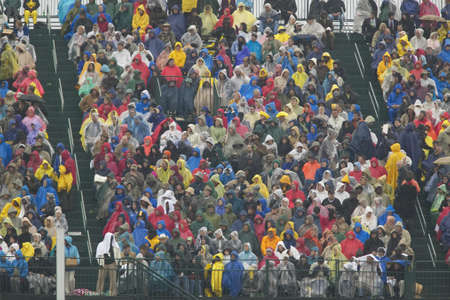 Rain gear clad guests attend the official opening ceremony of the Clinton Presidential Library November 18, 2004 in Little Rock, AK