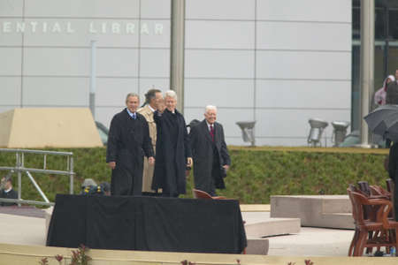 accompanied: Former U.S. President Bill Clinton waves from the stage accompanied by President George W. Bush, former presidents Jimmy Carter and George H. W. Bush during the official opening ceremony of the Clinton Presidential Library November 18, 2004 in Little Rock Editorial