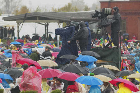 Guests hold umbrellas in the rain as cameramen record the official opening ceremony of the Clinton Presidential Library November 18, 2004 in Little Rock, AK
