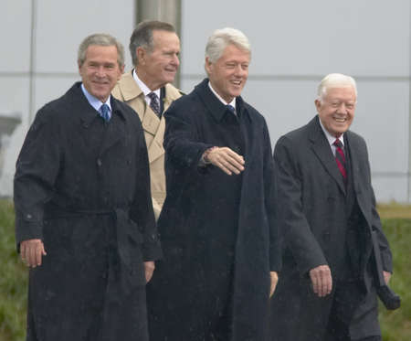 Former U.S. President Bill Clinton waves from the stage accompanied by President George W. Bush, former presidents Jimmy Carter and George H. W. Bush during the official opening ceremony of the Clinton Presidential Library November 18, 2004 in Little Rock Editoriali