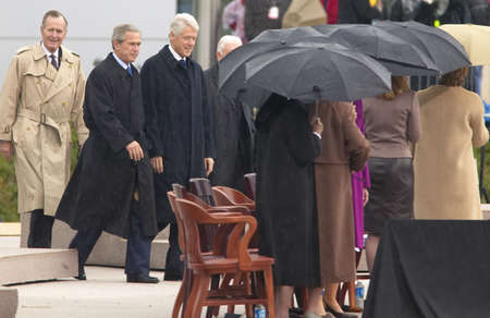 accompanied: Former U.S. President Bill Clinton walks on the stage accompanied by President George W. Bush, former presidents Jimmy Carter and George H. W. Bush during the official opening ceremony of the Clinton Presidential Library November 18, 2004 in Little Rock,
