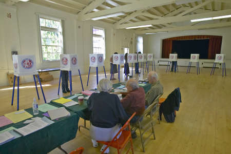 Election volunteers and voting booths in a polling place, CA
