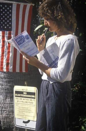 voter: Woman voter reading election Sample Ballot at the entrance to a polling place, CA Editorial