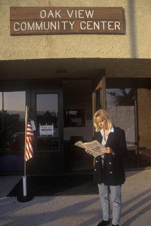 encuestando: Mujer votantes lectura panfleto electoral en la entrada a un lugar de votaci�n, CA