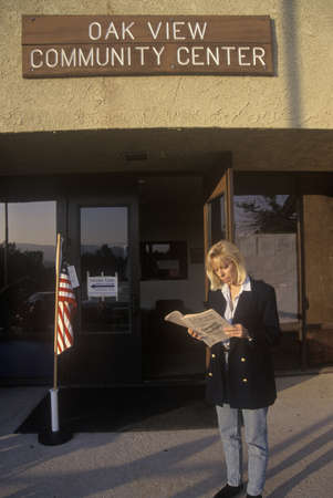 polling: Woman voter reading election pamphlet at the entrance to a polling place, CA