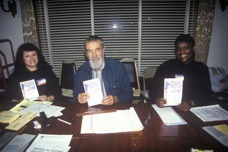 encuestando: Voluntarios electorales mostrando boletas de muestra en un lugar de votaci�n, CA Editorial