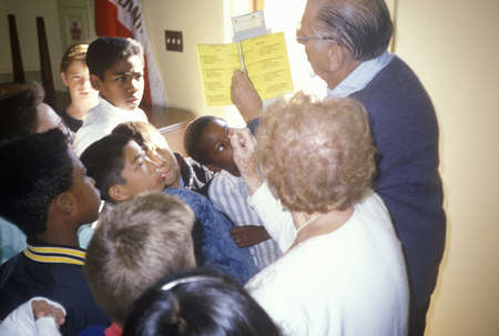 instructing: Election volunteers instructing young people on voting procedures in a polling place, CA
