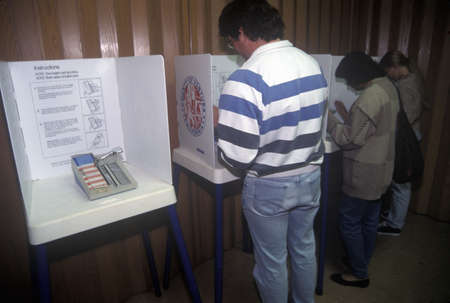 voting: Voters and voting booths in a polling place, CA Editorial