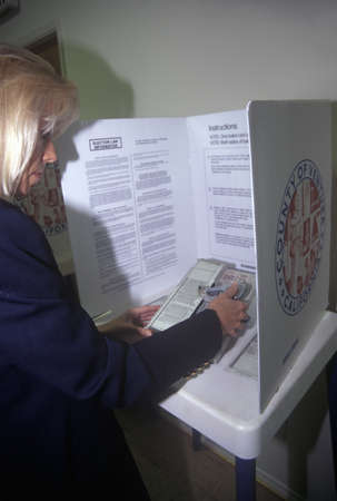 voter: Woman voter in a voting booth selecting choices on a ballot, CA Editorial
