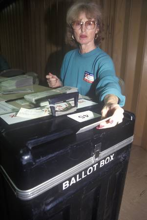 polling: Election volunteer depositing ballots in a ballot box in a polling place, CA