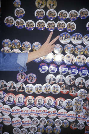 A hand making a V symbol in front of rows of Clinton/Gore political campaign buttons Redactioneel