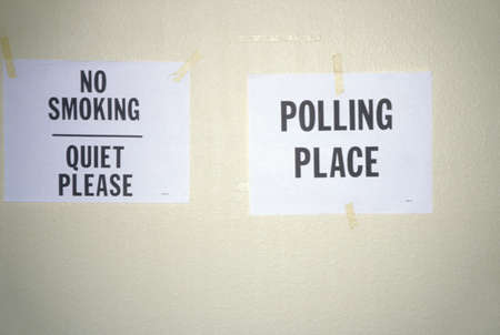 Signs taped to the wall in a polling place read No Smoking and Polling Place