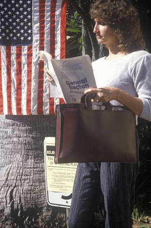 voter: Woman voter reading election pamphlet at the entrance to a polling place, CA
