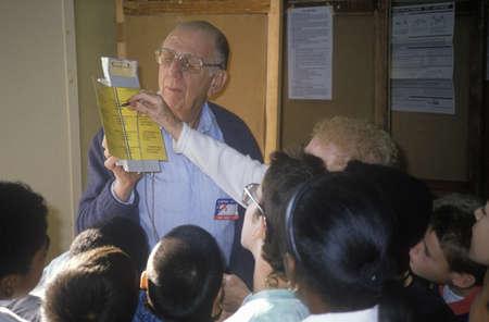 encuestando: Voluntarios electorales instruir a los j�venes sobre los procedimientos de votaci�n en un colegio electoral, CA