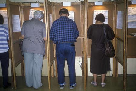 encuestando: Votantes y las cabinas de votaci�n en un colegio electoral, CA
