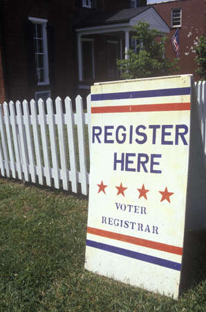 voter registration: Sign in front of white picket fence reads Register Here, VA
