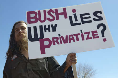 political and social issues: Protestor in Tucson Arizona of President George W. Bush holding a sign protesting his Iraq foreign policy