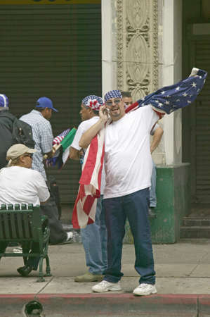 Hispanic man on cellphone with American flag participates in march for Immigrants and Mexicans protesting against Illegal Immigration reform by U.S. Congress, Los Angeles, CA, May 1, 2006 Editöryel