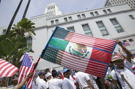 political and social issues: Mexican flag is superimposed over American flag in front of City Hall, Los Angeles, while hundreds of thousands of immigrants participate in march for Immigrants and Mexicans protesting against Illegal Immigration reform by U.S. Congress, Los Angeles, CA, Editorial