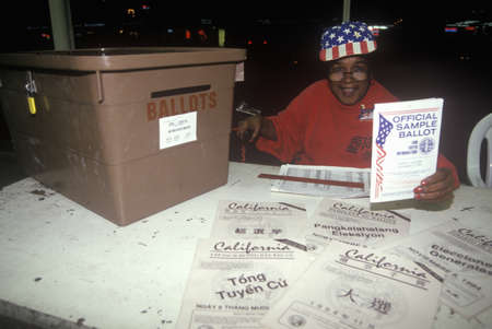 Election volunteer and ballot box in a polling place, CA