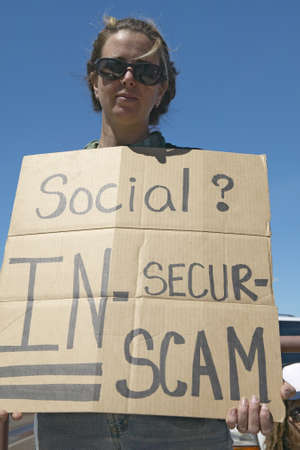 domestic policy: Protestor of President George W. Bush holding a sign up protesting his Social Security plan, in Tucson Arizona Editorial