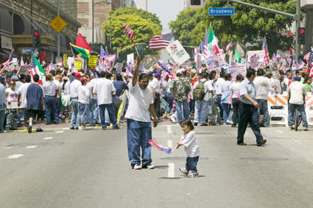 daughter in law: Hispanic girl and father with American flag watch hundreds of thousands of immigrants participating in march for Immigrants and Mexicans protesting against Illegal Immigration reform by U.S. Congress, Los Angeles, CA, May 1, 2006 Editorial