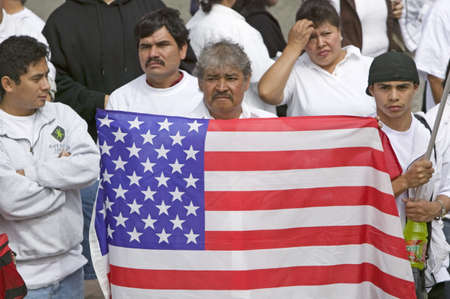 rallying: Latin American man holds US flag with hundreds of thousands of immigrants participating in march for Immigrants and Mexicans protesting against Illegal Immigration reform by U.S. Congress, Los Angeles, CA, May 1, 2006