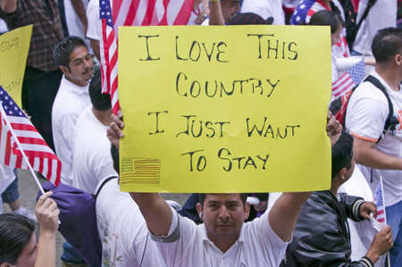 hundreds and thousands: Man holds sign saying I love this country along with hundreds of thousands of immigrants participating in march for Immigrants and Mexicans protesting against Illegal Immigration reform by U.S. Congress, Los Angeles, CA, May 1, 2006 Editorial