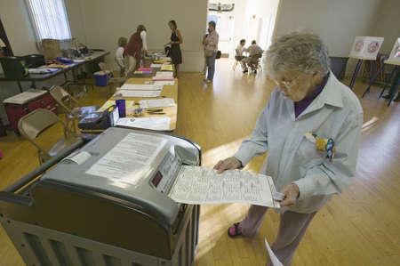 Senior vrouw inserts ingevuld stembiljet voor Congres verkiezingen, november 2006, in een elektronische scanner in Ojai, Ventura County, Californië