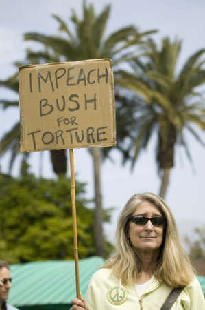 political and social issues: A woman holds a sign saying Impeach Bush for torture at an anti-Iraq War protest march in Santa Barbara, California on March 17, 2007 Editorial