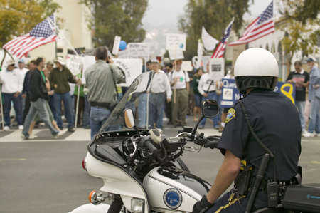A motorcycle policeman looks at protesters against George W. Bush and the Iraq War at an anti-Iraq War protest march in Santa Barbara, California on March 17, 2007