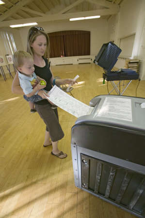 electronic voting: Young mother and Baby (Sophia Larson) inserts completed ballot for Congressional election, November 2006, into an electronic scanner in Ojai, Ventura County, California