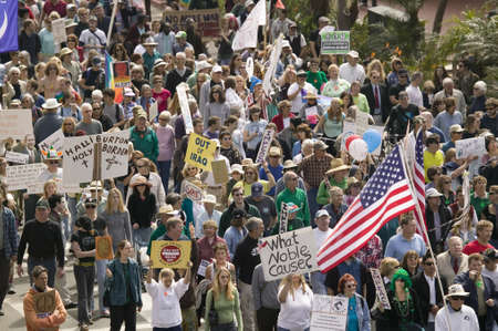 A large crowd of protesters march and chant down State Street carrying signs at an anti-Iraq War protest march in Santa Barbara, California on March 17, 2007