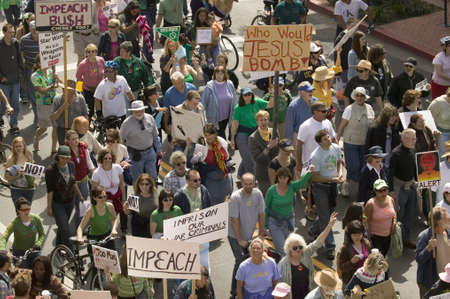political and social issues: A large crowd of protesters march and chant down State Street carrying signs at an anti-Iraq War protest march in Santa Barbara, California on March 17, 2007