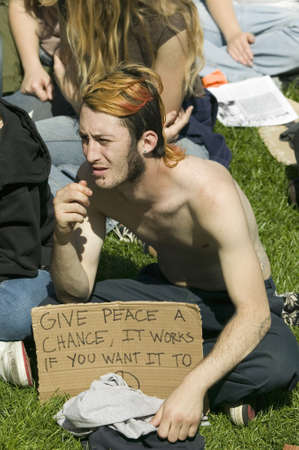 political and social issues: A hippy has Give Peace A Chance slogan on his protest sign at an anti-Iraq War protest march in Santa Barbara, California on March 17, 2007