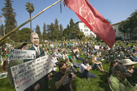 political and social issues: A cutout of George W. Bush saying Mission Accomplished is seen with a crowd of protesters and a red peace flag at an anti-Iraq War protest march in Santa Barbara, California on March 17, 2007 Editorial