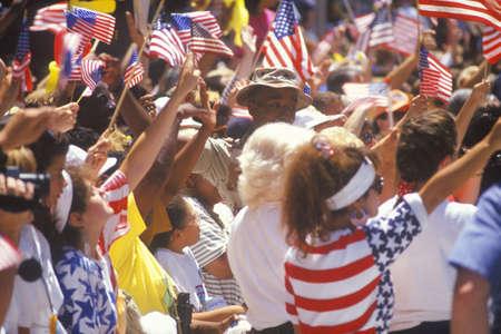 drapeaux am�ricain: Spectateurs ondulant les drapeaux am�ricains, D�fil� sous les confettis, New York City, New York