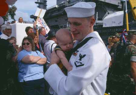 homecoming: American Sailor Holding Baby After Returning Home From Sea, San Diego, California Editorial