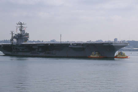 towed: United States Aircraft Carrier Being Towed Into Harbor